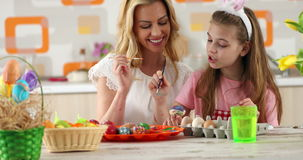 Easter painting – mother with daughter coloring eggs stock footage