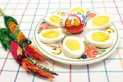 Easter palm, halves of eggs and painted egg on colorful plate Royalty Free Stock Photography