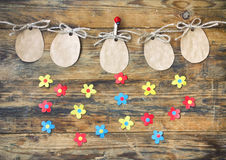 Easter paper tag shape of an egg hanging on rope, applique flowe Royalty Free Stock Photo