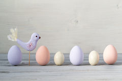 Easter pastel colored eggs and purple hand made bird on a light wooden background Royalty Free Stock Images