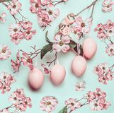 Easter pastel pink pattern with hanged eggs and decor blossom on turquoise. Background Stock Photo