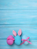 Easter pink and blue eggs with bunny ears. On wooden background Royalty Free Stock Images
