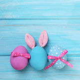 Easter pink and blue eggs with bunny ears. On wooden background Royalty Free Stock Photos