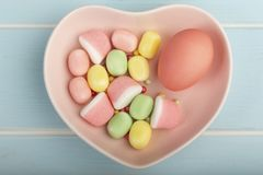 Easter pink egg on a plate in the form of heart with candies stock photo