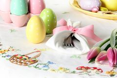 Easter place setting on an elegant linen table cloth. This traditional holiday brunch place setting includes painted eggs, an stock photography