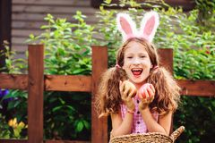 Easter portrait of happy child girl in funny bunny ears playing egg hunt outdoor royalty free stock photography