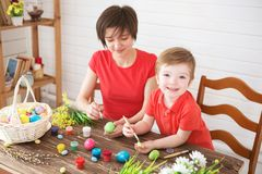 Easter preparations. Happy young mother spending time with her joyful son. Happy family Mom and children son paint easter eggs stock images