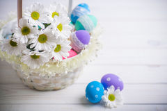 Easter present basket with white flowers and colored eggs on wooden background spring inspiration Royalty Free Stock Photos