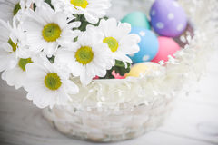 Easter present basket with white flowers and colored eggs on wooden background spring inspiration Stock Photo