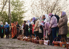 At Easter, the priest blesses the people with baskets and candle Royalty Free Stock Photography