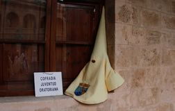 Easter procession penitent hood before the neghborhood procession in mallorca. An easter procession penitent hood stands on a window before the start of a Stock Photo