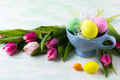 Easter purple, pink, green, yellow eggs in blue cup and pink tul. Ips background. Copy space. Happy Easter greeting card or invitation Stock Image