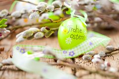 Easter Pussy-willow and Easter egg on wooden background. Happy. Easter card. with Happy Easter text in german royalty free stock images