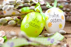 Easter Pussy-willow and Easter egg on wooden background. Happy. Easter card. with Happy Easter text in german royalty free stock image