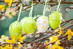 Easter Pussy-willow and Easter egg on wooden background. Happy. Easter card. with Happy Easter text in german stock photo