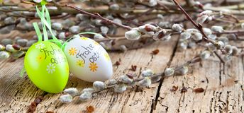 Easter Pussy-willow and Easter egg on wooden background. Happy. Easter card. with Happy Easter text in german stock photography