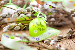 Easter Pussy-willow and Easter egg on wooden background. Happy. Easter card. with Happy Easter text in german stock image