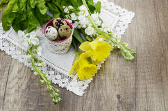 Easter quail eggs on a linen napkin, beautiful narcissus. And white blossoms Royalty Free Stock Photo