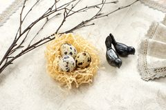 Easter quail eggs in a nest and branches of willow on a light background royalty free stock image