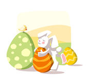 Easter rabbit. Holding an egg which is colored similary to a carrot Royalty Free Stock Images