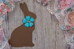 Easter rabbit background. Brown Easter rabbit on a wood background with vintage lace Stock Photography