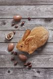 Easter rabbit with chocolate eggs on wooden background stock photo