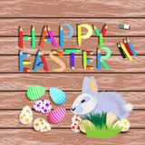 Easter. Easter rabbit with colored. Eggs in polka dots and stripes. on a wooden background. pencil inscription Stock Photos