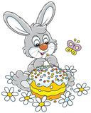 Bunny with an Easter cake. Easter rabbit with a colorfully decorated holiday pie among flowers, a vector illustration in a cartoon style Royalty Free Stock Photos
