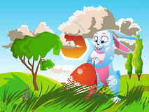 Easter rabbit with an egg. Is on the grass on a background of a spring landscape. Festive  cartoon illustration Royalty Free Stock Photos