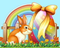 Easter rabbit with egg in the yard Royalty Free Stock Photo
