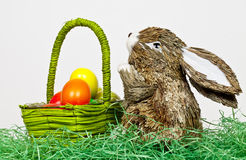 Easter Rabbit with eggs. A rabbit brings some colorful eggs in a basket stock photo