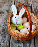 Easter rabbit and eggs in basket Stock Photos
