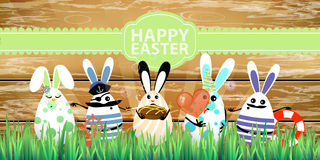 Easter. Rabbit-eggs with funny cute faces. In the grass. On a wooden fence background. Holiday with candy sailors. Inscription on a green ribbon. Illustration Royalty Free Stock Image
