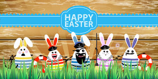 Easter. Rabbit-eggs with funny cute faces. In the grass. On a wooden fence background. Sailors five pieces with a captain at the head and an inscription with a Stock Photography