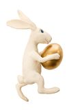 Easter rabbit with gold egg. White toy rabbit with gold egg.The image contains a path Stock Photos