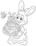 Bunny with an Easter cake. Easter rabbit holding a freshly backed and decorated holiday cake, a black and white vector illustration for a coloring book Royalty Free Stock Images