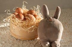 Easter rabbit inside a sieve full of easter eggs on rustic wood. En stock photo