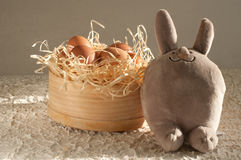 Easter rabbit inside a sieve full of easter eggs on rustic wood Royalty Free Stock Images