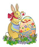 The easter rabbit paints egg Stock Image