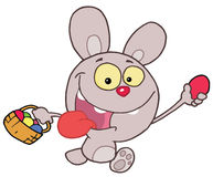 Easter Rabbit Running And Holding Up An Egg Stock Images