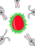 Easter rabbits. Red Easter egg in grass nest with several looking out rabbits Royalty Free Stock Photo