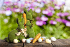 Easter Rabbits Eggs Carrots. Decorative rabbits on wood surface with spring flowers blurred in background. One rabbit standing and holding decorative carrot. One Stock Photo