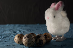 Easter rabbits,quail eggs on blue background. close up. Selective focus Royalty Free Stock Image