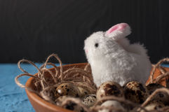 Easter rabbits and quail eggs in wooden bowl on background close up Stock Images