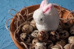 Easter rabbits and quail eggs in wooden bowl on background close up. Easter rabbits and quail eggs in wooden bowl on blue background close up Stock Image