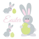 Easter Rabbits Set. Set of cute cartoon easter rabbits. Bunny holding an egg, paints an egg, looking at an egg Stock Images