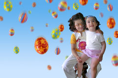 Easter Rain. Two smiling little girls under a colorful Easter eggs rain Stock Photo