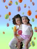 Easter Rain Vertical. Two smiling little girls under a colorful Easter eggs rain Stock Images