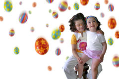 Easter Rain in white. Two smiling little girls under a colorful Easter eggs rain Royalty Free Stock Image