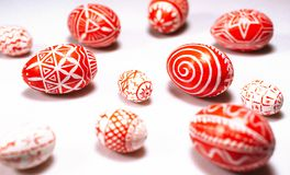 Easter red eggs with folk ukrainian white pattern scattered on white background. Closeup royalty free stock photos